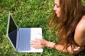 Hermosa chica con un ordenador portátil al aire libre — Foto de Stock
