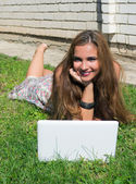 Beautiful girl with a laptop outdoor — Stock Photo