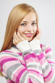 Beautiful girl in colored sweater on a light background — Stok fotoğraf