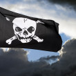 Stock Photo: Jolly Roger (pirate flag) against storm clouds