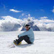 Snowboarder resting on the ski slope - Stock Photo