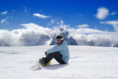 Snowboarder resting on the ski slope — Stock Photo