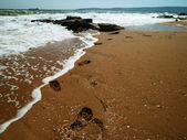 Sea surf and footprint over sand — Stock Photo