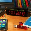 Clock with Happy New Year! message on table — Stok fotoğraf