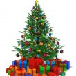 Decorated Christmas tree with heap of color gift boxes - Stock Photo