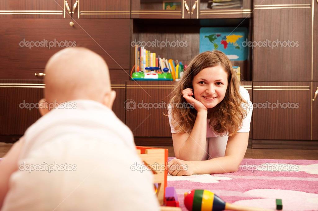 Young mother is playing with her baby n playroom — Stock Photo #7628914