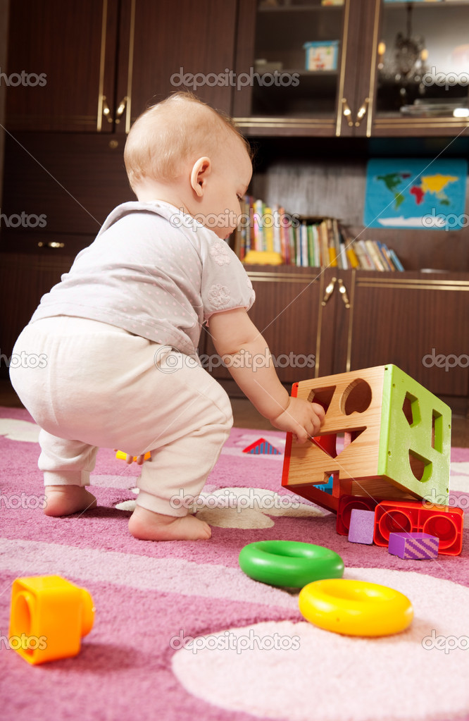 Little girl aged one playing with toy blocks on the floor — Stock Photo #7641778