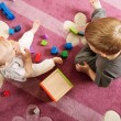 Brother and sister playing with toy blocks — 图库照片