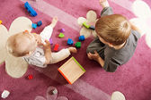 Brother and sister playing with toy blocks — Stock Photo