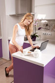 Pregnant woman with laptop in kitchen — Stock Photo