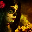Artistic shot of sugar skull girl with dead roses — Stock Photo