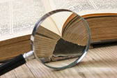 Old book and magnifying glass — Stock Photo
