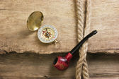 Old tobacco pipe and compass — Stock Photo