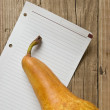 Pear and a note  on a wooden background - 