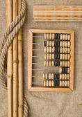 Old wooden abacus on the background of bagging — Stock Photo