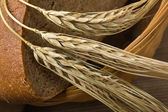 Rebanadas de pan de centeno y mazorcas de maíz en una mesa de madera — Foto de Stock