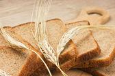 Rebanadas de pan de centeno y mazorcas de maíz en la mesa de madera — Foto de Stock