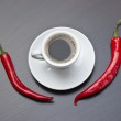 Coffee cup and red peppers — Stock Photo