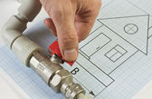 Plumbing fittings in hand on drawing — Stockfoto