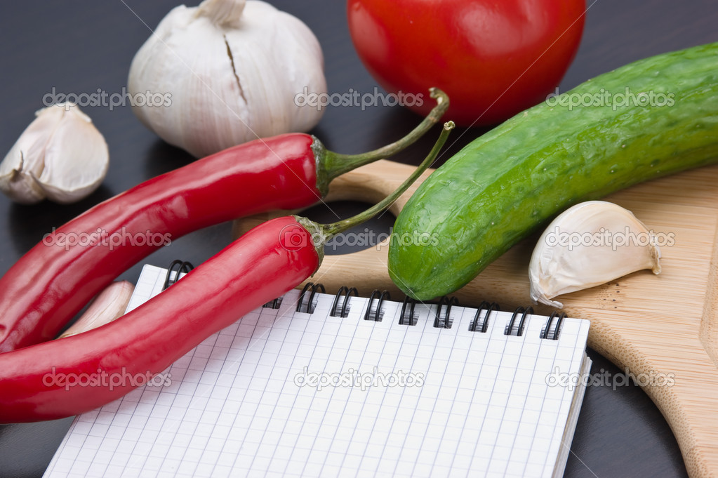 Notebook for cooking recipes and vegetables on a cutting board — Stock Photo #6950966