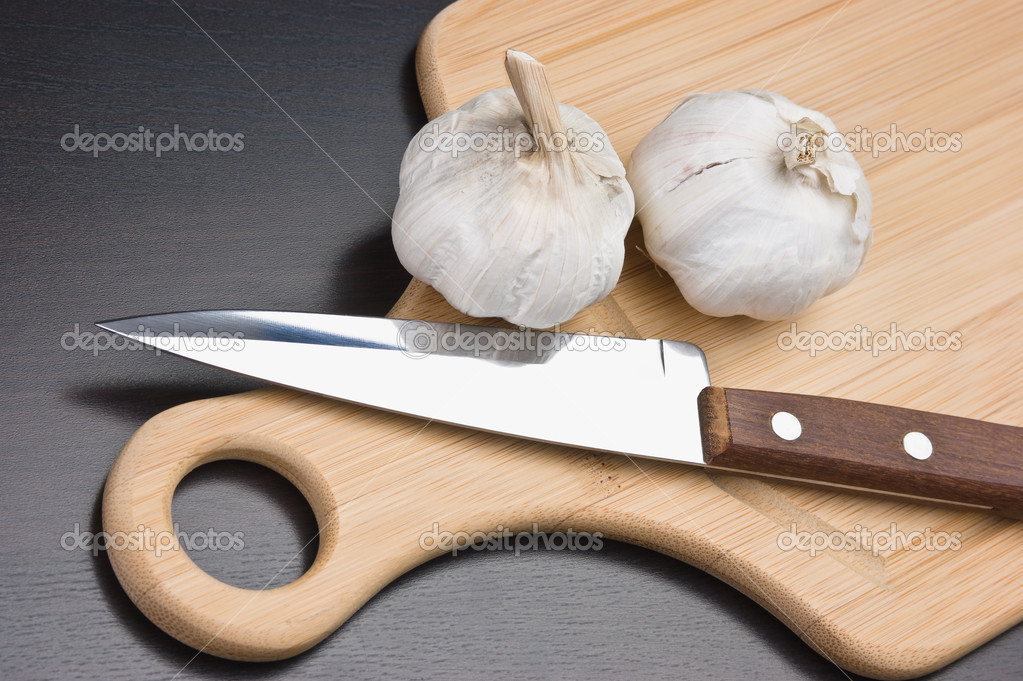 Garlic and knife on a kitchen cutting board — Stock Photo #6950996
