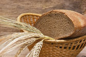 Rye bread and ears of corn in basket — Stock Photo