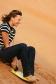 Teen girl riding on the sand dunes sandboard — Stock Photo