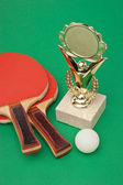 Sports awards and tennis racquets on green table — Stock Photo