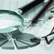 Stock Photo: Magnifying glass and working paper