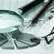 Magnifying glass and working paper - Stock Photo
