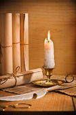 Antic candle with rool of paper — Stock Photo