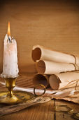 Candle and old roll of paper — Stock Photo