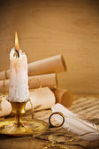 Old candle on table with rolls of paper — Stock Photo