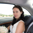 Smiling bride sitting in the car - Stock Photo