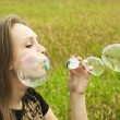 Young girl sitting on the grass and blowing soap bubbles — Stockfoto