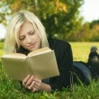 Beautiful girl reading in park on grass — Stock Photo