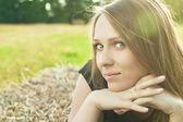 молодая девушка лежит на heystack и улыбается — Стоковое фото
