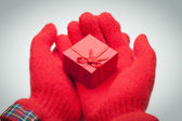 Hands giving red box with present over grey background — Stock Photo