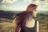 Beautiful girl upland with hair blown by wind — Stock Photo