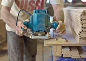 Home improvement - handyman sanding wooden floor in workshop — Stok fotoğraf