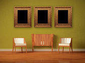 Two luxurious chairs with wooden console and picture frames in green interior — Stock Photo