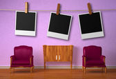 Two luxurious chairs with wooden console and hangings instant photos frames — Stock Photo