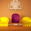 Two yellow chairs with a purple chair with the glass chandelier — Stock Photo