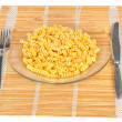 Macaroni in a transparent plate on straw mat — Stock Photo