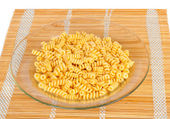 Macaroni in a transparent plate on straw mat — Foto Stock