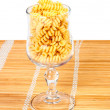 Macaroni in a glass on straw mat - Stock Photo