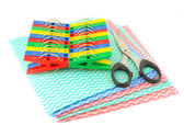 Color clothes-pegs and scissors on the color napkins — 图库照片