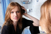 Young woman in bath at front of a mirror correcting hairs — Stock Photo