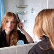 Young womin bath at front of mirror correcting hairs — Stock Photo #6818242