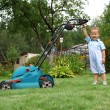 Little Boy Gardener mowing the lawn — 图库照片